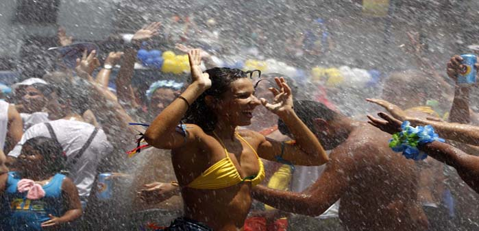 "Water is sprinkled on revellers to help them cool off during an annual block party known as ""Escravos da Maua"", one of the many carnival parties to take place in the neighbourhoods of Rio de Janeiro February 3, 2013. (Pilar Olivares/Reuters)"